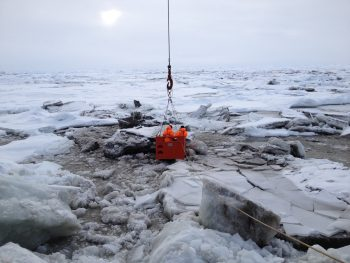 Figure 5. This image shows sediment-rich sea ice in the Transpolar Drift. Two researchers were lowered by crane from the decks of the icebreaker RV Polarstern to the surface of the ice to collect samples. Photo Credit: R. Stein, AWI, 2014.