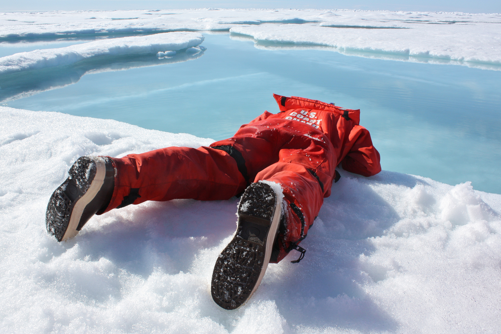 Photograph of a researcher sipping water from a sea ice melt pond