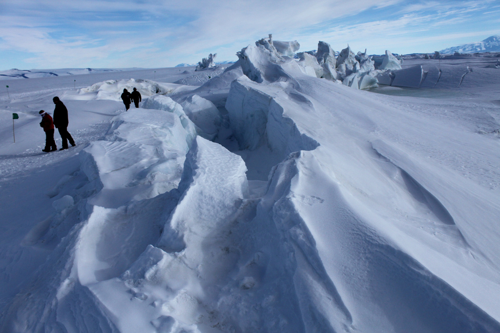 Photograph of people on sea ice near pressure ridges