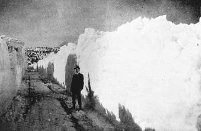 Man standing on cleared train tracks after a snowstorm in 1917