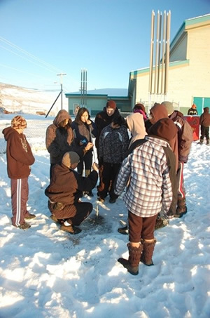 Children gather around a drill in front of a school