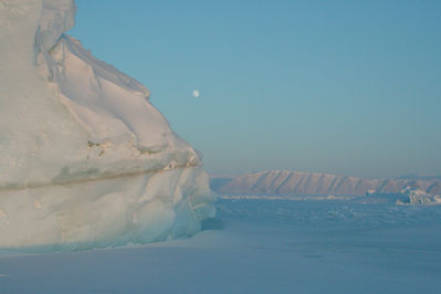 The sun sets and moon rises behind icebergs and sea ice