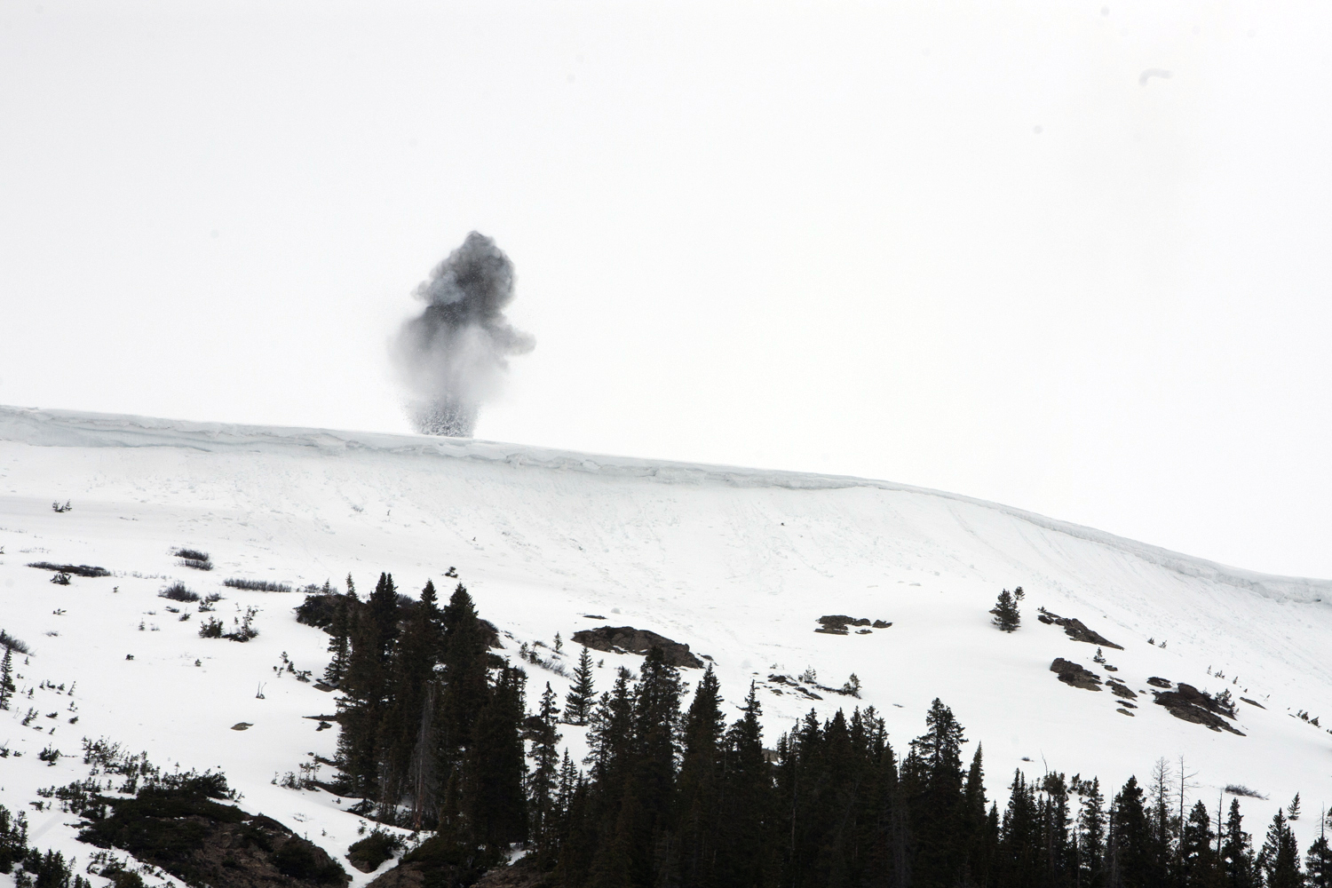 Photograph of a charge detonating high on a snowy slope in Colorado