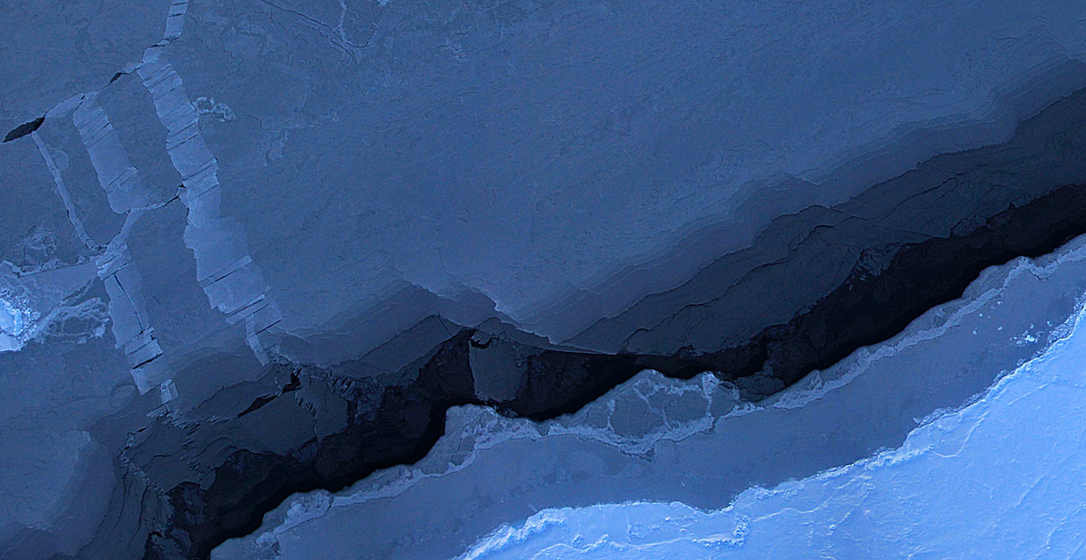 This photo is a mosaic image of sea ice in the Beaufort Sea, created by the Digital Mapping System (DMS) instrument aboard the NASA IceBridge P-3B. The dark area in the middle of the image is open water seen through a lead, or opening, in the ice. Light blue areas are thick sea ice and dark blue areas are thinner ice formed as water in the lead refreezes. Leads are formed when cracks develop in sea ice as it moves in response to wind and ocean currents.