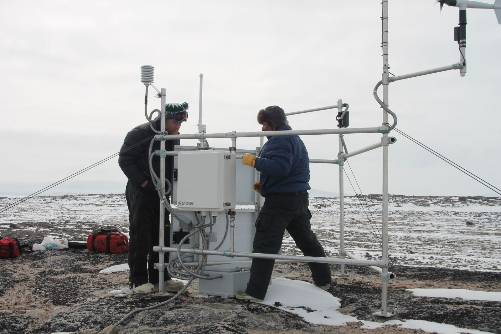Esa Qillaq (right) and Kelly Elder check out the Ailaktalik weather station during annual maintenance.