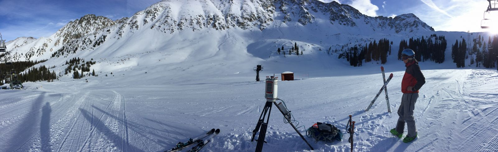 Photograph of a researcher scanning snow depth