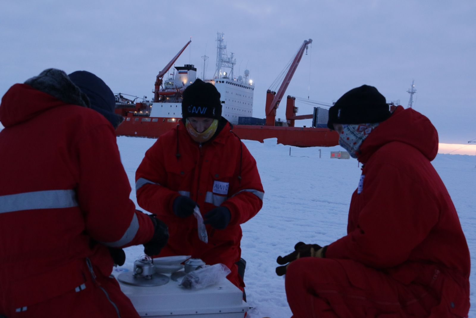 MOSAiC School participants set up a radiometer on the sea ice. Radiometers were used to calibrate the sensors on each of the three meteorological stations. From left to right: Alex Mavrovic, Sean Horvath, and Tatiana Matveeva.