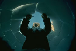 Inuit man building an igloo; silhouette