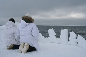 Two Inuit kneel on ice floe and look at the sky