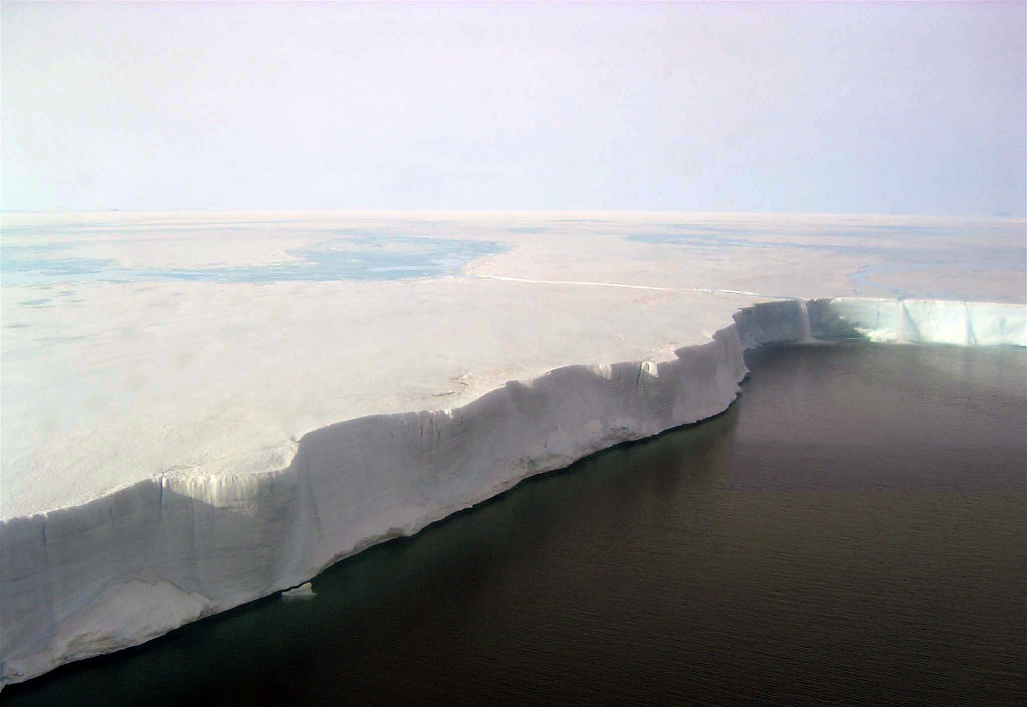 This in-flight photo shows the edge of the Larsen B Ice Shelf. The surface is melted, and ice flows off the edge like a waterfall. Photo Credit: Ted Scambos and Rob Bauer, NSIDC