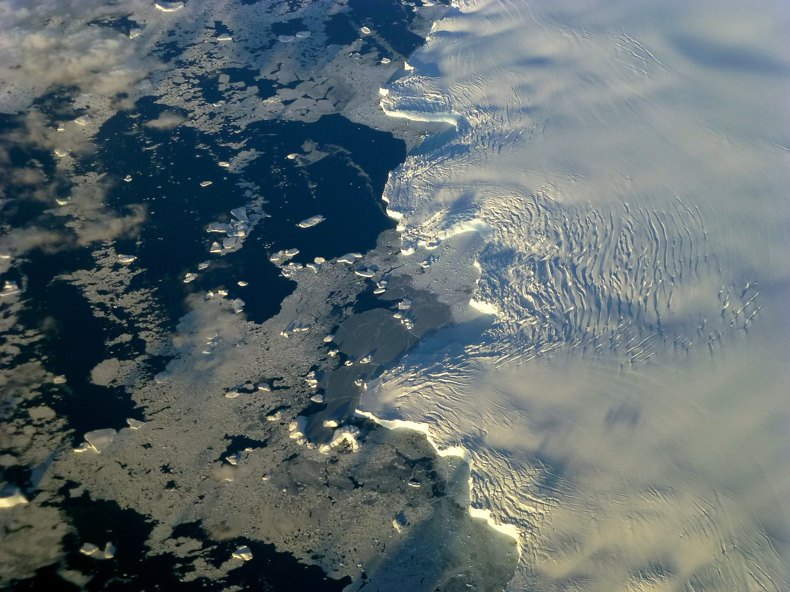 The edge of an ice shelf stretches out to the ocean off of Adelaide Island near the Antarctic Peninsula. The photo was taken during NASA's IceBridge mission. Credit: Maria-Jose Vinas, NASA