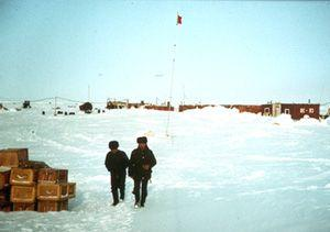 "Two station members walking through the base camp of the high-latitude Sever expedition at Zhokov Island. Image credit: EWG. (<a href=""/cryosphere/gallery/photo/34070"">View photo detail.</a>) <br>"