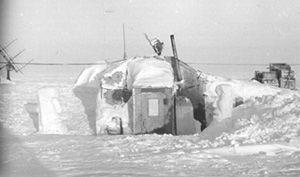 "Although summers posed the hazards of melt water, the winters posed problems with deeply drifting snow. In winter, windblown snow had to be cleared from the entrance of this aerological (radiosounding) hut. Image credit: EWG. (<a href=""/cryosphere/gallery/photo/34078"">View photo detail.</a>) <br>"