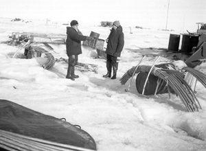 "Due to changes in the ice floe surface, it was not uncommon for camps to relocate to more stable ground. This photograph was taken during the rebuilding of the camp NP-22 in 1980. Aluminum tent poles are at the right, and an overturned boat is at the left. Image credit: EWG. (<a href=""/cryosphere/gallery/photo/34080"">View photo detail.</a>) <br>"