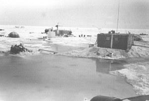 "Here, melt ponds encroach on many of the buildings in the camp. Sometimes, inflatable boats were used for transportation. Image credit: EWG. (<a href=""/cryosphere/gallery/photo/34084"">View photo detail.</a>) <br>"