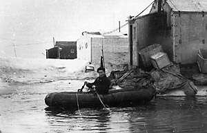 "During summer, melt ponds posed hazards to the camp. Here, a station member rows an inflatable raft in a melt pond that has formed in the middle of the camp at NP-6. Image credit: EWG. (<a href=""/cryosphere/gallery/photo/34087"">View photo detail.</a>) <br>"