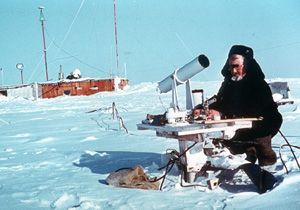 "One of the primary purposes of the drifting stations was to collect all possible meteorological data while on the ice floe. This involved installing, calibrating, and maintaining the instruments. Here, researcher German Maximov conducts a routine calibration of a pyranometer (in the large tube). Image credit: EWG. (<a href=""/cryosphere/gallery/photo/34085"">View photo detail.</a>) <br>"