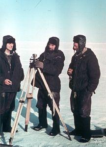 "Determining instrument location by theodolite. A theodolite is a high-precision surveying instrument. Because the ice floes rotated and changed in topography as they drifted, undergoing freezing and thawing, station members needed to regularly determine the position of the instruments relative to each other and to North. Image credit: EWG. (<a href=""/cryosphere/gallery/photo/34091"">View photo detail.</a>) <br>"