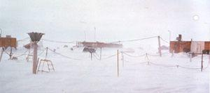 "A closer view of the instrument array at NP-21. The camp buildings in the background are just visible through the blowing snow. Image credit: EWG. (<a href=""/cryosphere/gallery/photo/34101"">View photo detail.</a>) <br>"