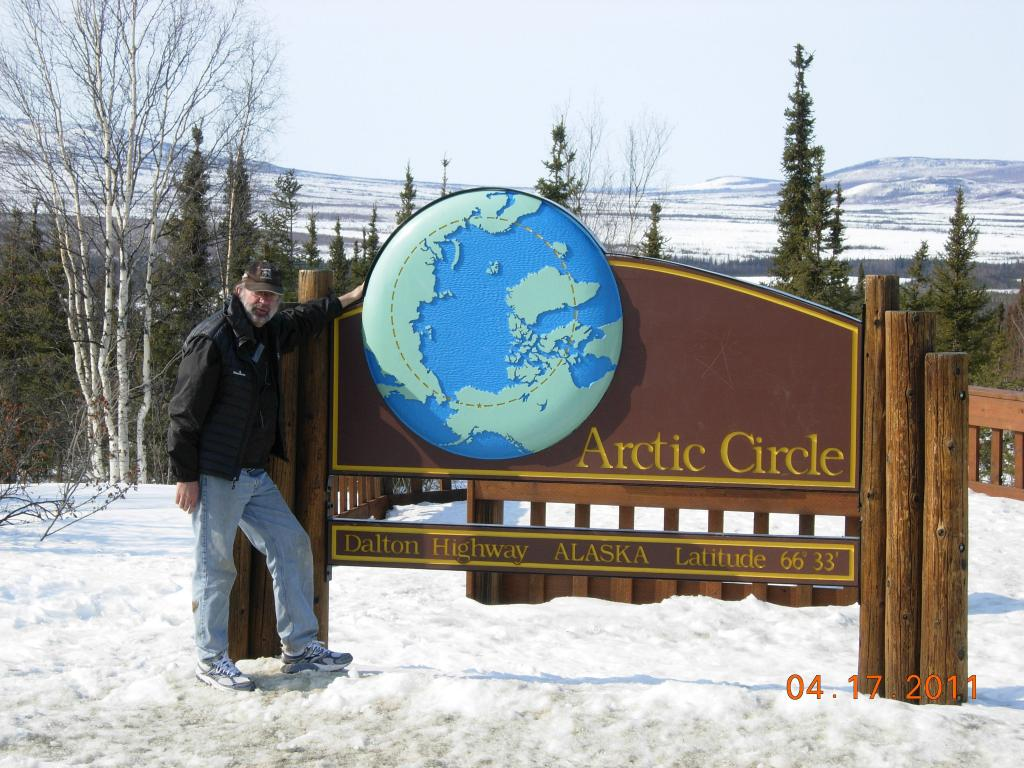 "NSIDC director poses at the sign marking the Arctic Circle along the Dalton Highway in Alaska, during the 2011 Arctic Observing Network project. (<a href=""/cryosphere/gallery/photo/33972"">View photo detail.</a>) <br>"