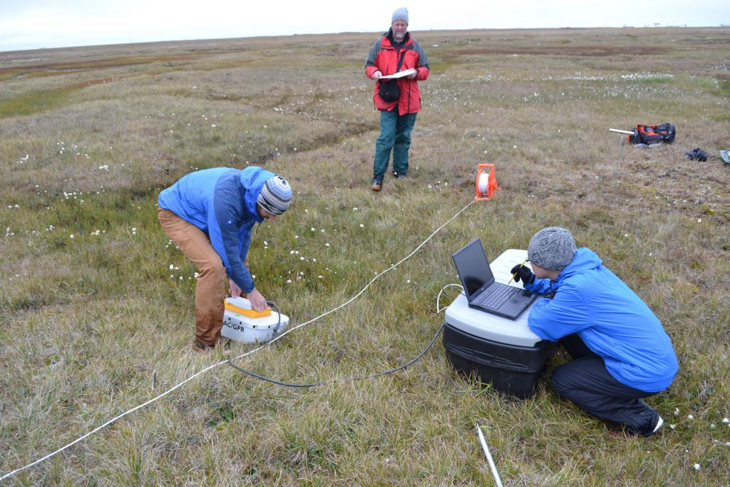 "Andy Parsekian, Kevin Schaefer, and Lin Liu use a ground penetrating radar to measure the depth of an ice wedge on August 15, 2013. The survey line lies perpendicular to the ice wedge and similar ice wedges crisscross the tundra in the background (Credit: Elchin Jafarov, NSIDC). (<a href=""/cryosphere/gallery/photo/34154"">View photo detail.</a>) <br>"