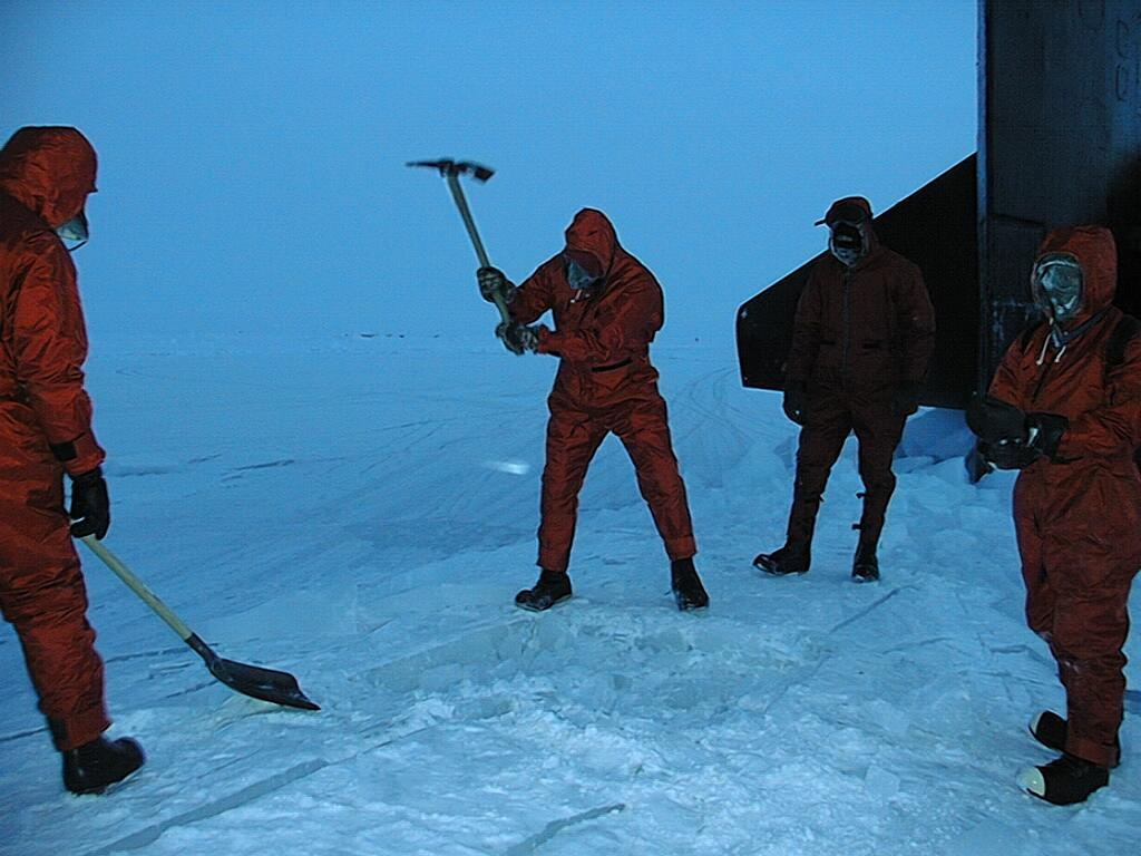 "Members of Ice Camp Lyon chip away the sea ice to access the hatch of the USS Hawkbill after it surfaces during SCICEX 99. Photo courtesy of ASL. (<a href=""/cryosphere/gallery/photo/34002"">View photo detail.</a>) <br>"