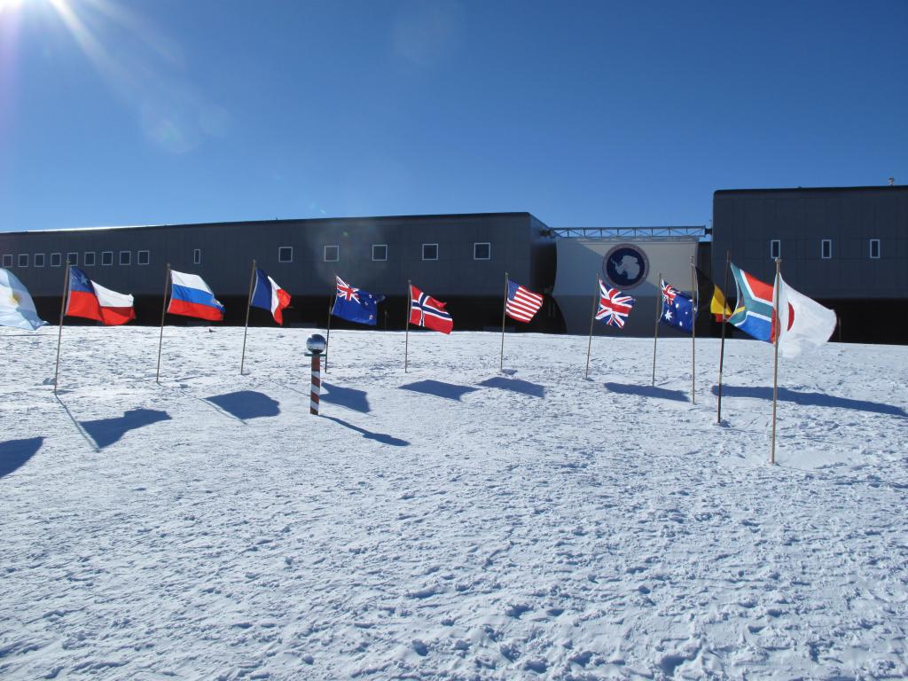 "The ceremonial South Pole is marked by flags and a pole. The real South Pole is a few hundred feet away. Image Credit: Ted Scambos, NSIDC (<a href=""/cryosphere/gallery/photo/33784"">View photo detail.</a>) <br>"
