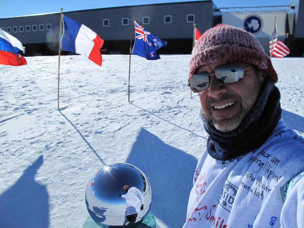 "Ted Scambos poses at the ceremonial South Pole, with South Pole station in the background. Image Credit: Ted Scambos, NSIDC (<a href=""/cryosphere/gallery/photo/33787"">View photo detail.</a>) <br>"