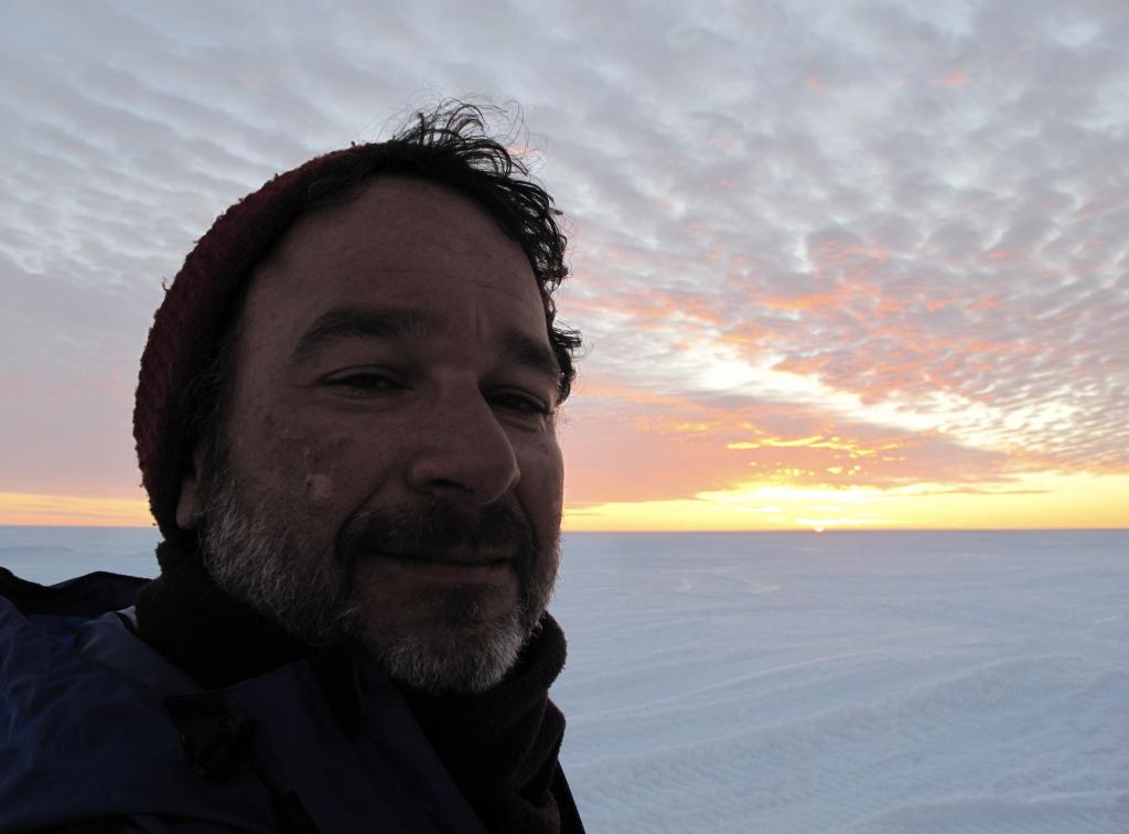 "Ted Scambos smiles, with the Antarctic sunset in the background. Image Credit:  Ted Scambos, NSIDC (<a href=""/cryosphere/gallery/photo/33885"">View photo detail.</a>) <br>"