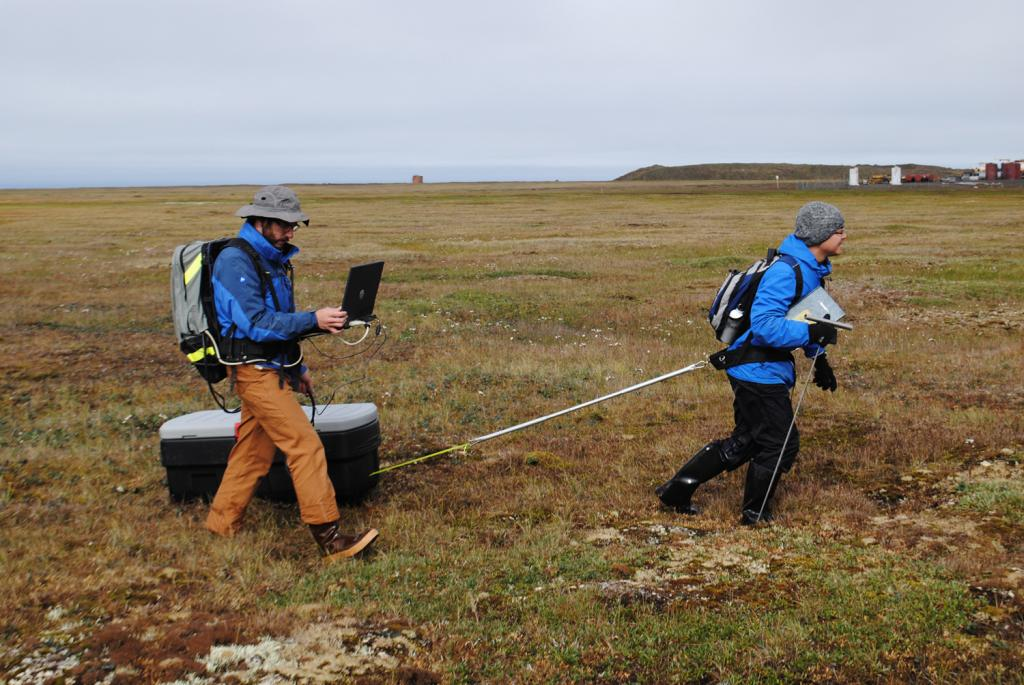 "Lin Liu pulls a ground penetrating radar unit through the tundra near Barrow, Alaska on  to measure the active layer depth. The radar unit (in the box) emits a pulse which reflects off the permafrost to measure the active layer depth, which is recorded in the computer held by Andy Parsekian. (Credit: Kevin Schaefer, NSIDC) (<a href=""/cryosphere/gallery/photo/34156"">View photo detail.</a>) <br>"