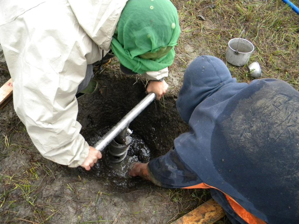 "Standford University scientist Lin Liu and research volunteer Tim Schaefer are attempting to remove a drill bit that accidently froze into the permafrost at a site just south of Deadhorse, Alaska on July 11, 2009. The researchers spent eight hours chipping the drill bit out of the permafrost using a crowbar, pry bar, and a hammer (Credit: Kevin Schaefer, NSIDC) (<a href=""/cryosphere/gallery/photo/34184"">View photo detail.</a>) <br>"