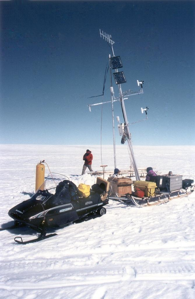 "A leaning weather station that has slowly started to melt out of the ice in recent years. We have snow-mobiled here (a one-hour trip) to steam-drill a new 6-meter (20-foot) hole and secure the station into it. Photo by John Maurer, CIRES/NSIDC, University of Colorado. (<a href=""/cryosphere/gallery/photo/33159"">View photo detail.</a>) <br>"