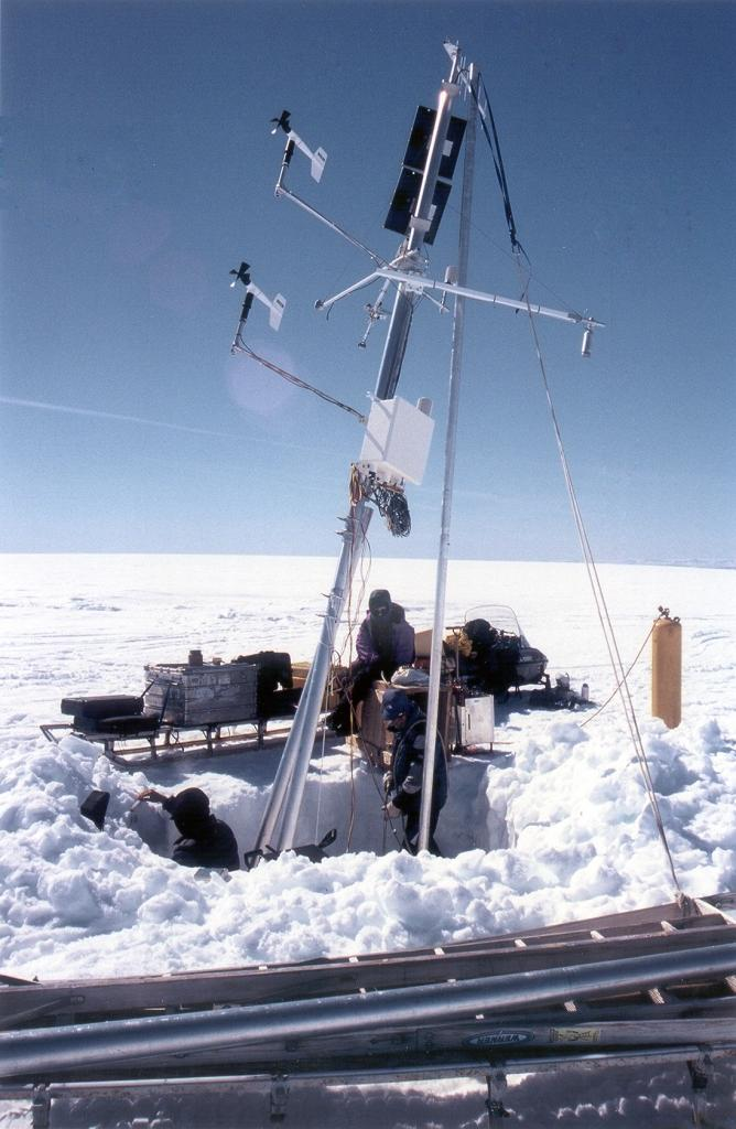 "Another view of us working on this weather station. Nic is making measurements of the snow at the left, Koni is steam-drilling, and Betsy Kolbert is observing. Photo by John Maurer, CIRES/NSIDC, University of Colorado. (<a href=""/cryosphere/gallery/photo/33160"">View photo detail.</a>) <br>"
