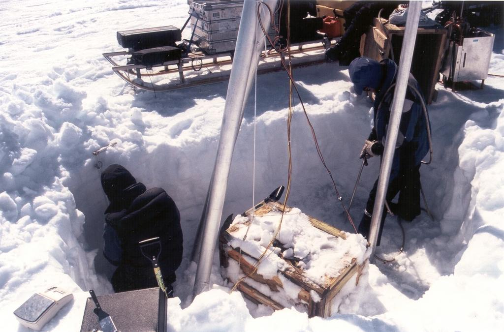 "Another view of Nic making measurements in the snow (temperature and density profiles) and Koni steam-drilling. The wooden box contains batteries that run the instruments on the weather station. Photo by John Maurer, CIRES/NSIDC, University of Colorado. (<a href=""/cryosphere/gallery/photo/33162"">View photo detail.</a>) <br>"