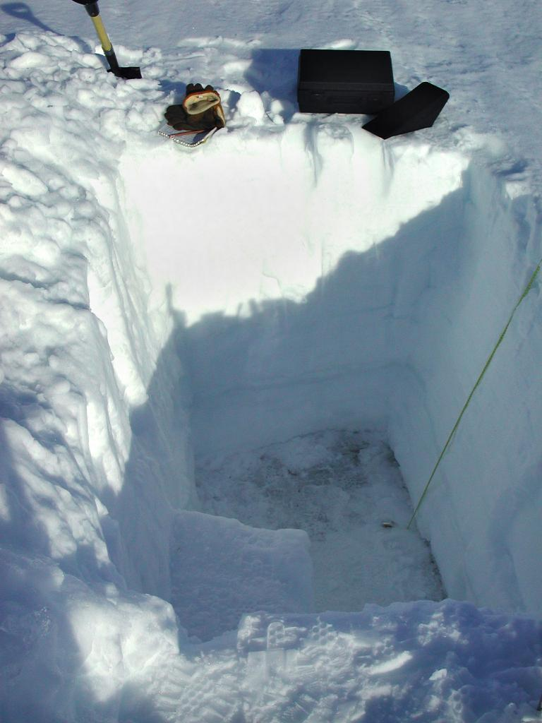 "Another close-up of the snow pit. You can see the floor of the pit better in this shot where there is darker ice. The yellow strip is a measuring tape. Photo by John Maurer, CIRES/NSIDC, University of Colorado. (<a href=""/cryosphere/gallery/photo/33165"">View photo detail.</a>) <br>"