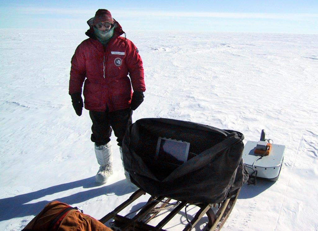 "Ted Scambos poses with the GPS/GPR surveying system used during the Antarctic Megadunes expedition. Image Credit:  Courtesy Ted Scambos and Rob Bauer, NSIDC  <a href=""http://nsidc.org/antarctica/megadunes/"">Megadunes Web site</a> (<a href=""/cryosphere/gallery/photo/33029"">View photo detail.</a>) <br>"