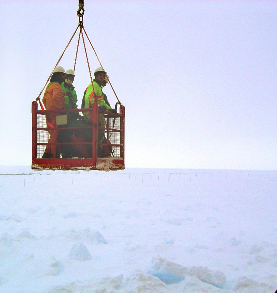 "One of several teams aboard the Aurora Australis, being lowered in the basket so that can start their research. Photo Credit: Courtesy Ted Scambos, NSIDC (<a href=""/cryosphere/gallery/photo/33199"">View photo detail.</a>) <br>"