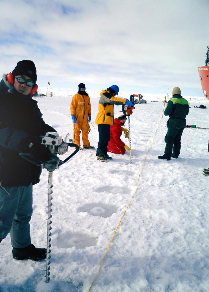 "Terry Haran (center, middleground) drilling core samples with the team. Photo Credit: Courtesy Ted Scambos, NSIDC (<a href=""/cryosphere/gallery/photo/33217"">View photo detail.</a>) <br>"