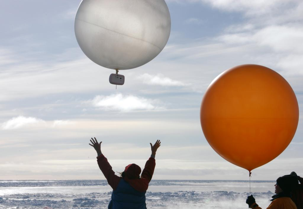 "Nina Brudermann releasing one of her balloons into the sky; each balloon has an insulated video camera attached. Photo Credit: Courtesy Ted Scambos, NSIDC (<a href=""/cryosphere/gallery/photo/33245"">View photo detail.</a>) <br>"