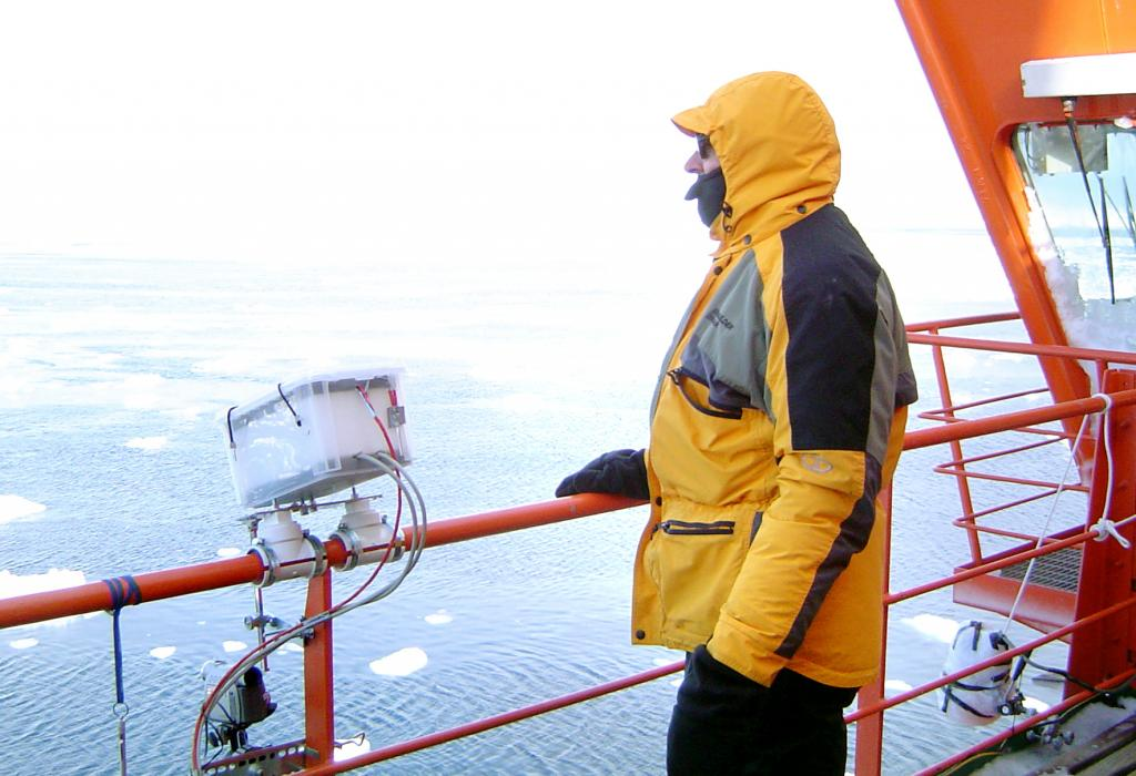 "Terry Haran with the Heitronics KT-19.82 thermal radiometer, mounted to the port side rail of the Aurora Australis, to measure the skin temperature of the sea icePhoto Credit: Courtesy Ted Scambos, NSIDC (<a href=""/cryosphere/gallery/photo/33265"">View photo detail.</a>) <br>"