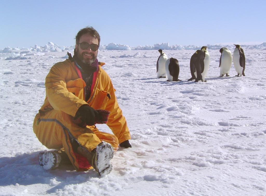 "Ted Scambos, taking a break with the emperor penguins. Photo Credit: Courtesy Ted Scambos, NSIDC (<a href=""/cryosphere/gallery/photo/33270"">View photo detail.</a>) <br>"
