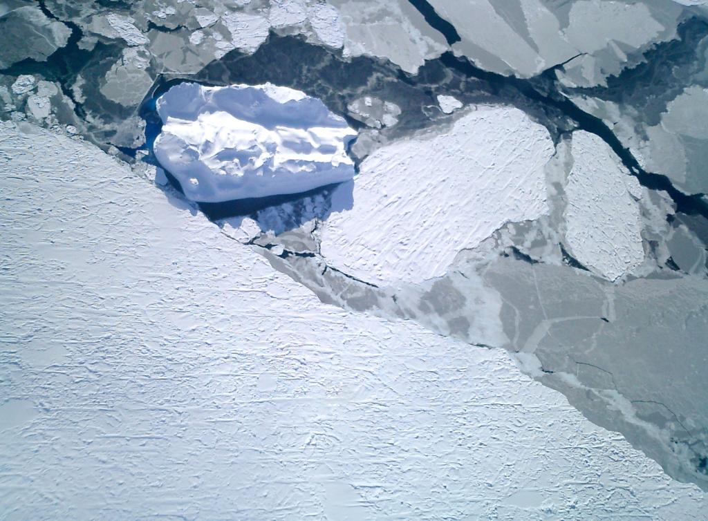 "An airborne view of the overlapping nila blended into the smooth snow-covered sea ice, which an iceberg in the middle. Photo Credit: Courtesy Ted Scambos, NSIDC (<a href=""/cryosphere/gallery/photo/33276"">View photo detail.</a>) <br>"