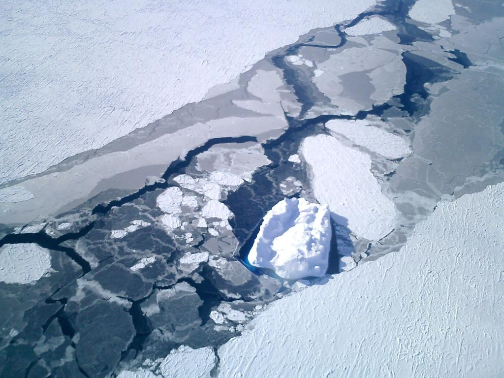 "An airborne view of the overlapping nila blended into the smooth snow-covered sea ice, which an iceberg at center. Photo Credit: NSIDC Courtesy Anthony Petty (<a href=""/cryosphere/gallery/photo/33280"">View photo detail.</a>) <br>"