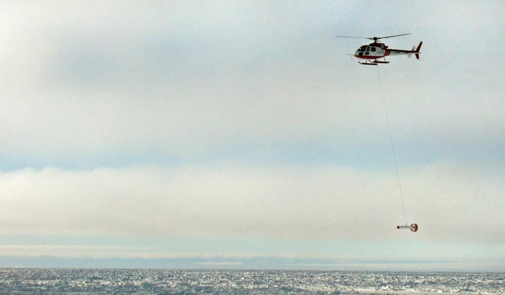"The AWI self-developed Helicopter EM Sensor in action beneath the AS350 Squirrel. Photo Credit: NSIDC Courtesy Alice O'Connor (<a href=""/cryosphere/gallery/photo/33283"">View photo detail.</a>) <br>"