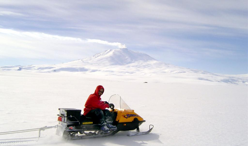 "Ted Scambos on his snowmobile with Mt. Erebus in the background. Image Credit:  Courtesy Ted Scambos and Rob Bauer, NSIDC  <a href=""http://nsidc.org/antarctica/megadunes/"">Megadunes Web site</a> (<a href=""/cryosphere/gallery/photo/33049"">View photo detail.</a>) <br>"