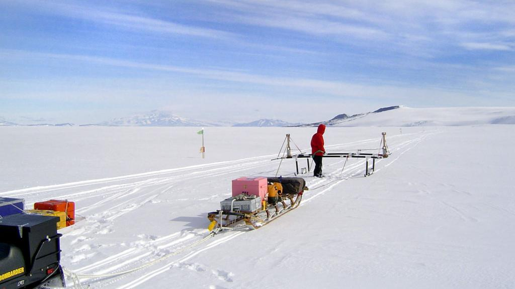 "Ted Scambos with the GPS/GPR surveying system, Mount Discovery in the background. Image Credit:  Courtesy Ted Scambos and Rob Bauer, NSIDC  <a href=""https://nsidc.org/antarctica/megadunes/"">Megadunes Web site</a> (<a href=""/cryosphere/gallery/photo/33050"">View photo detail.</a>) <br>"