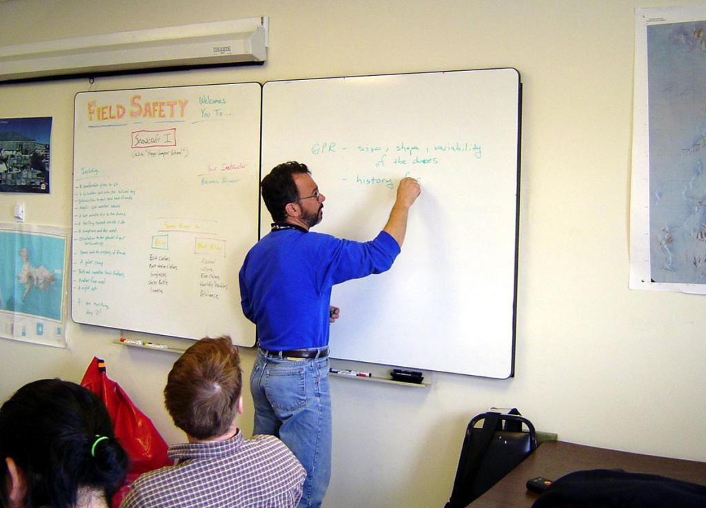 "Ted Scambos (at the white board), leading the meeting at McMurdo Station. Image Credit:  Courtesy Ted Scambos and Rob Bauer, NSIDC  <a href=""http://nsidc.org/antarctica/megadunes/"">Megadunes Web site</a> (<a href=""/cryosphere/gallery/photo/33018"">View photo detail.</a>) <br>"