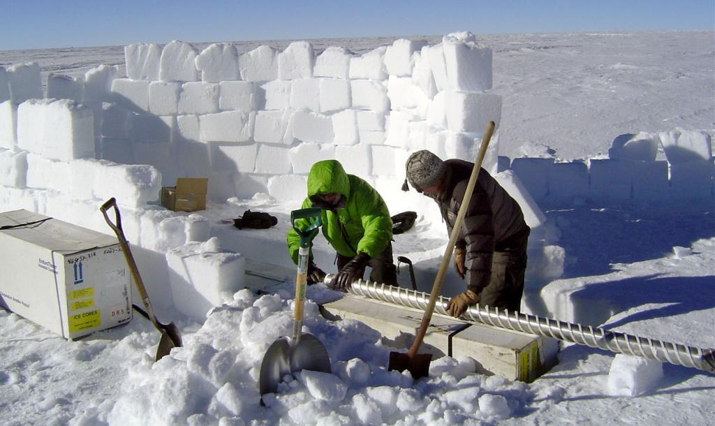 "Mac Cathles (left) and Zoe Courville (right) carefully removing the ice core sample from the drill. Image Credit:  NSIDC courtesy Ted Scambos and Rob Bauer. (<a href=""/cryosphere/gallery/photo/33070"">View photo detail.</a>) <br>"