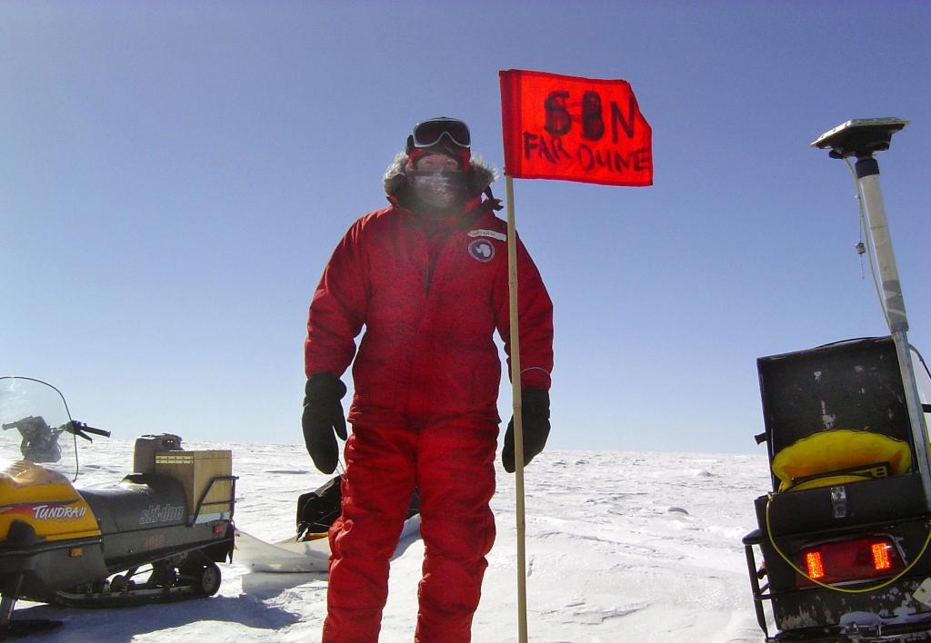 "Rob Bauer standing with the S3N Far Dune Flag, not to be misread as ""S8N"". Image Credit:  NSIDC courtesy Ted Scambos and Rob Bauer. (<a href=""/cryosphere/gallery/photo/33095"">View photo detail.</a>) <br>"