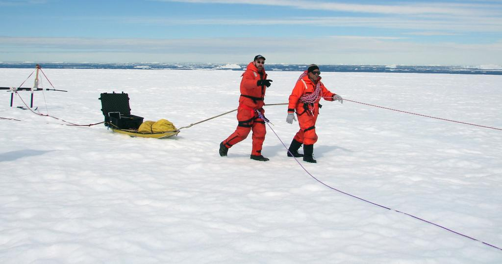 "Ronald Ross (left) and Pedro Skvarca (right) dragsthe sled across Chip, the test iceberg. Photo Credit: Courtesy Ted Scambos and Rob Bauer, NSIDC  <a href=""http://nsidc.org/icetrek"">IceTrek Web site</a> (<a href=""/cryosphere/gallery/photo/32892"">View photo detail.</a>) <br>"